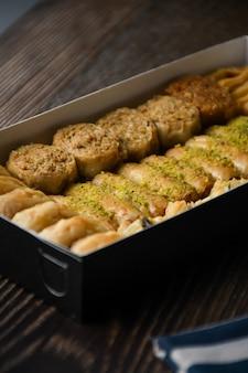 Schließen sie herauf türkisches baklava süßes gebäck mit honig im kasten lebensmittelhintergrund