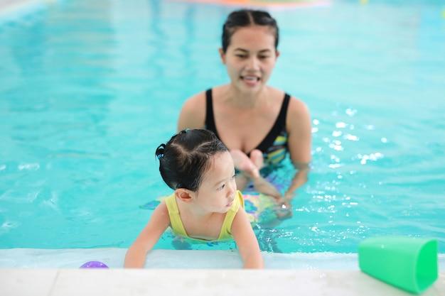 Schließen sie herauf unterrichtendes kind der mutter im swimmingpool