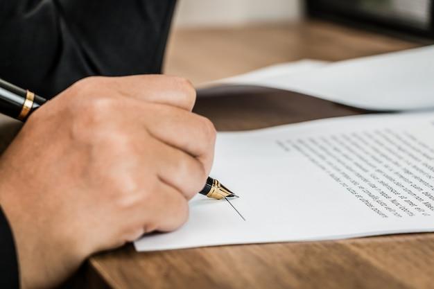 Schließen sie herauf unterzeichnende bedingungen der geschäftsfrau des vereinbarungsdokuments auf holztisch