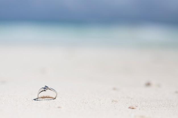 Schließen sie herauf verlobungsring im sand