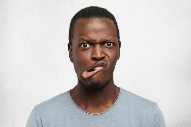 Schließen sie herauf verrückter doof junger afrikanischer mann, der münder macht, die stirn runzelt, mit erschrockenem erschrockenem blick starrt, drinnen an grauer wand posierend. menschliche mimik und emotionen
