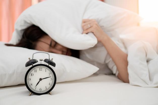 Schließen sie herauf wecker mit der faulen jungen asiatischen frau, die am frühen morgen für tägliche routinearbeit aufwacht.