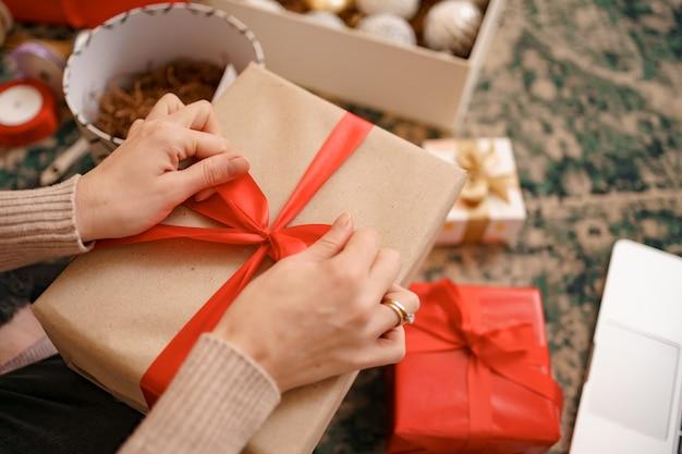 Schließen sie herauf weibliche hände, die einen roten bandbogen auf einer handwerksgeschenkbox binden.