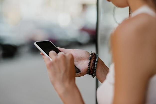 Schließen sie herauf weibliche hände mit den armbändern, die smartphone halten.
