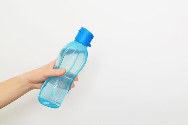 Schließen sie herauf weibliche hand, die eine flasche wasser auf weißem hintergrund hält.