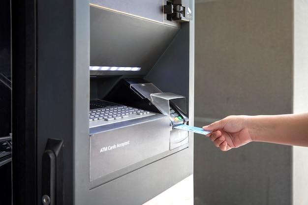 Schließen sie herauf weibliche hand unter verwendung der kreditkartebank von atm-maschine, um geld abzuheben