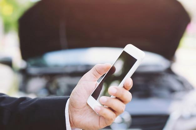 Schließen sie herauf weibliche hand unter verwendung eines mobilen smartphone-anrufs einen automechaniker, der um hilfe bittet