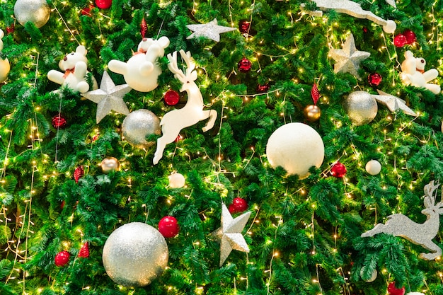 Schließen sie herauf weihnachtsbaumdekoration mit kugeln, silbernem stern und weißem rentier. weihnachtshintergrund.
