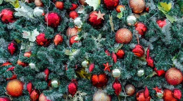 Schließen sie herauf weihnachtsbaumdekoration mit roter kugel, goldener kugel, goldener schneeflocke, roter stern. weihnachtshintergrund. weihnachten.
