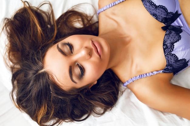 Schließen sie herauf zartes modeporträt des schönen mädchens mit perfekten langen haaren und natürlichem make-up, das auf dem bett in stilvollem seiden-bh liegt. romantische morgenstimmung.