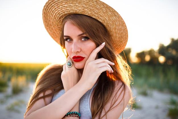 Schließen sie herauf zartes porträt der sinnlichen schönheitsfrau, die auf feld, weinlesestil, tragendem strohhut, naturschönheitsschminke, sommersprossiges gesicht und roten vollen lippen aufwirft.