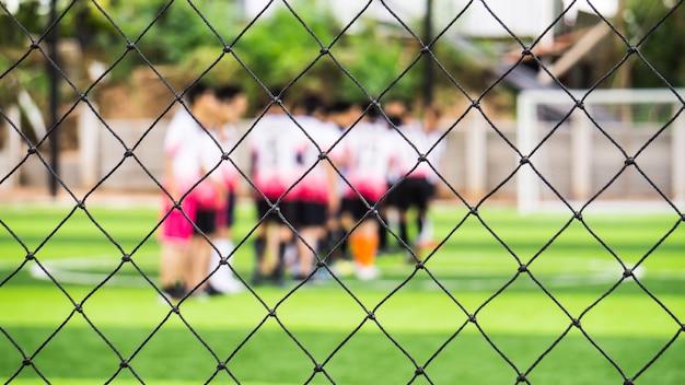 Schließen sie herauf zaun des hallenfußballfeldes des künstlichen grases für schützen sie den ball über fußballplatz.