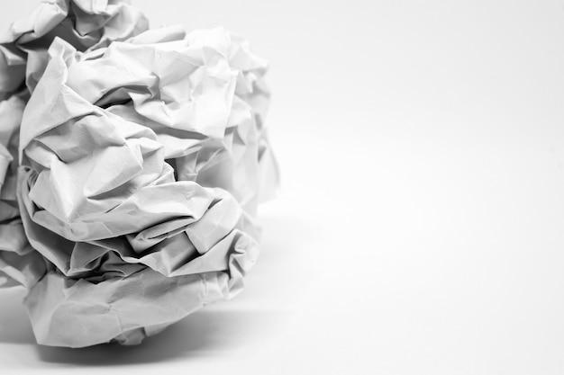 Schließen sie herauf zerknitterten papierball auf weiß