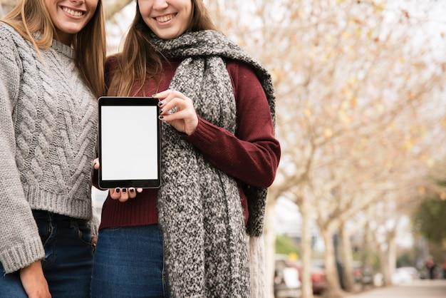 Schließen sie herauf zwei elegante frauen, die tablette in den händen halten