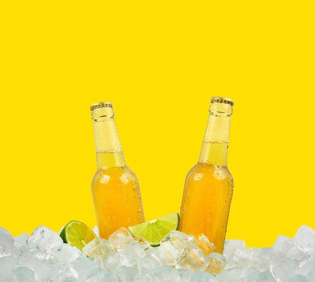 Schließen sie herauf zwei klare glasflaschen des kalten lagerbiers auf eiswürfeln im einzelhandel isoliert auf gelber wand, seitenansicht des niedrigen winkels