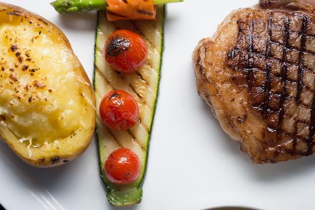 Schließen sie hida-beefsteak mit gegrillter tomate, karotte, gurke und spargel