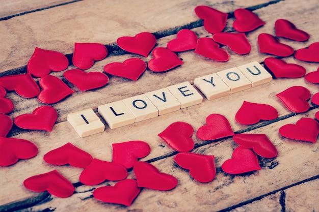 Schließen sie hölzerner text für ich liebe dich und rotes herz auf holzhintergrund.