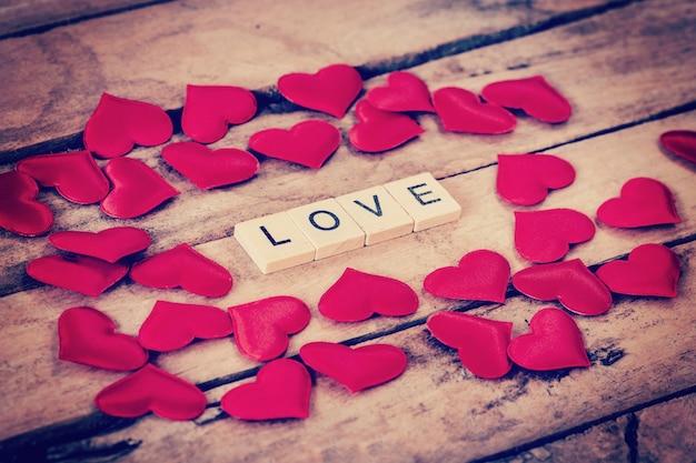 Schließen sie hölzerner text für liebe und rotes herz auf holzhintergrund