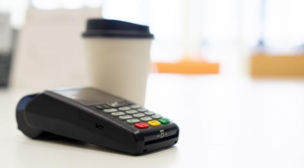 Schließen sie kreditkartenzahlungsmaschine bei tisch mit weißer kaffeetasse auf tisch im café, kontaktlose bezahlung