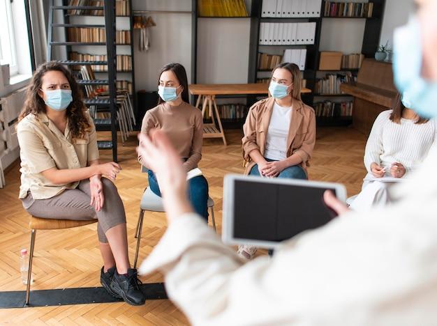 Schließen sie menschen mit masken bei der therapie
