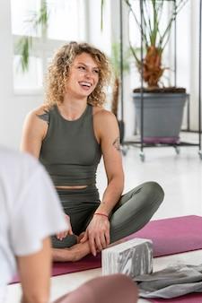 Schließen sie nah yogalehrer auf matte