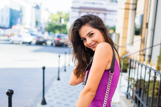 Schließen sie nahes atemberaubendes mädchen, das auf sonniger straße geht, sonniges wetter genießt, einkaufen, freunde wartet, um am wochenende tolle zeit zu haben. wellenförmige frisur. lila samt sexy kleid. romantische stimmung.