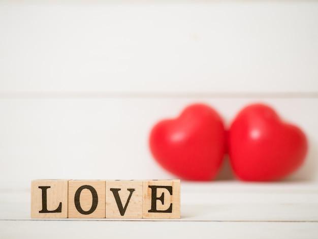 Schließen sie oben am wort liebe, liebe auf holzwürfel mit unscharfem rotem herzhintergrund. verwenden sie für valentinstag, liebe und beziehungskonzept.