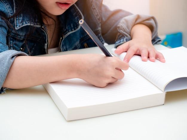 Schließen sie oben an den händen des kleinen mädchens, während sie den bleistift benutzen und auf notizbuch zeichnen