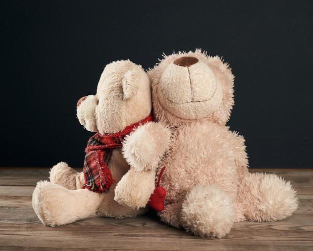 Schließen sie oben auf braunen teddybären, die auf einem braunen holztisch sitzen