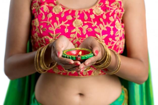 Schließen sie oben auf dem traditionellen indischen mädchen, das diya hält und diwali oder deepavali feiert