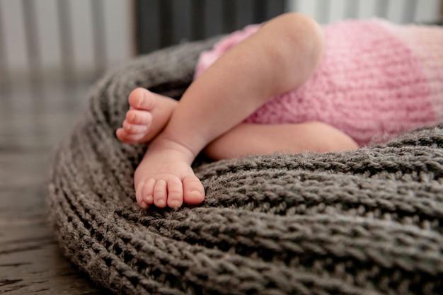 Schließen sie oben auf den beinen des babys in der flauschigen decke