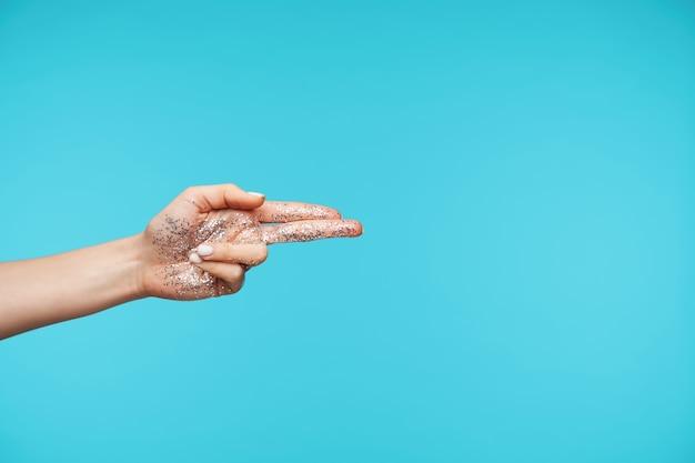 Schließen sie oben auf der eleganten hand, die palme mit glitzer zeigt, während isoliert