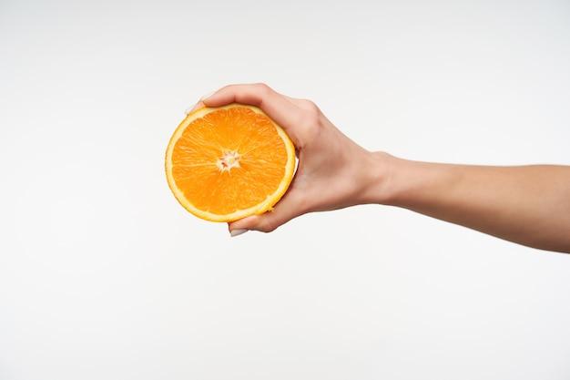 Schließen sie oben auf der hälfte der frischen orange, die von der hand der jungen frau gehalten wird