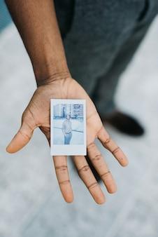 Schließen sie oben auf der hand des jungen hübschen schwarzen afroafrikaners, der ein polaroid von selbst zeigt