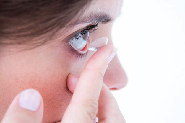 Schließen sie oben auf der hübschen frau, die kontaktlinse anwendet