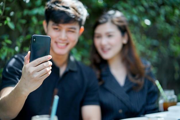 Schließen sie oben auf der mannhand, die smartphone hält, um foto (selfie) mit freundinnen zu machen