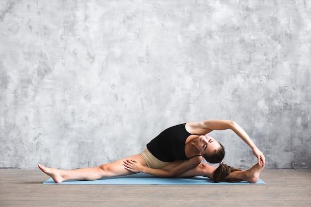 Schließen sie oben auf fitness yoga frau auf matte im fitnessstudio