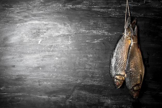Schließen sie oben auf frischem rohem fisch, der an einem seil hängt