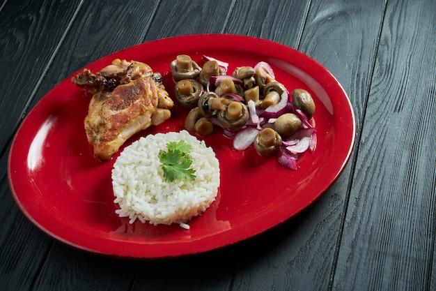 Schließen sie oben auf gekochtem reis mit eingelegten pilzen und huhn auf einem roten teller auf einem schwarzen holztisch. gesunde ernährung