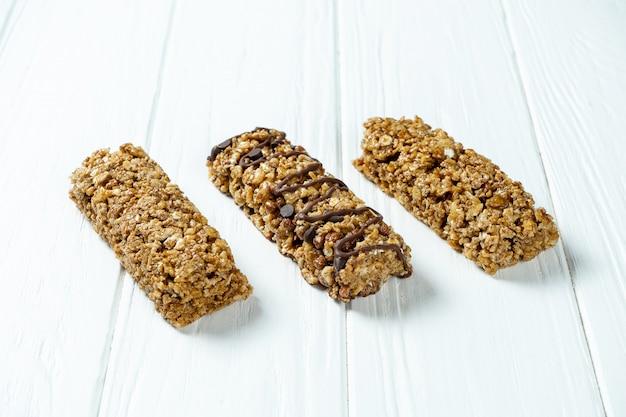 Schließen sie oben auf granola bar lokalisiert auf weißem holzhintergrund.