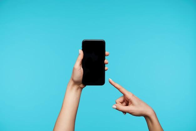 Schließen sie oben auf händen, die modernes mobiltelefon halten und auf schwarzem bildschirm isoliert zeigen