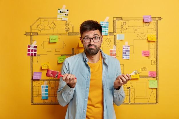 Schließen sie oben auf jungen designer, der bereit ist, neben hausmasterplanskizze zu renovieren