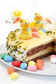 Schließen sie oben auf osterkuchen mit eiern und blumen auf holztisch