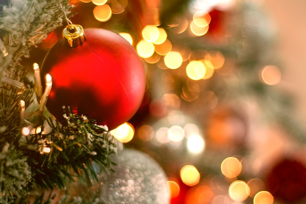 Schließen sie oben auf rotem ball auf weihnachtsbaum mit verschwommenen lichtern