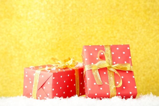 Schließen sie oben auf schönem rotem geschenk auf goldhintergrund