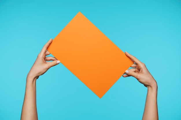 Schließen sie oben auf schönen händen, die leeres blatt papier halten