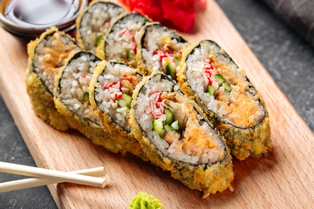 Schließen sie oben auf tempura-sushi-rollen mit käse und krabbenfleisch auf dem holzbrett