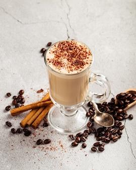 Schließen sie oben auf verziertem kaffee latte mit kakao in einem glasbecher auf dem konkreten hintergrund
