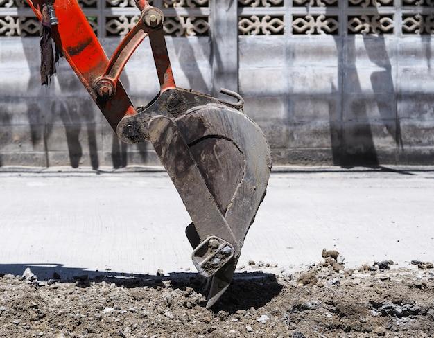 Schließen sie oben baggerschaufel, der auf dem boden für straßenbau im dorf gräbt.