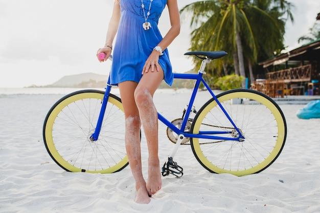 Schließen sie oben beine der attraktiven frau im blauen kleid, das auf tropischem strand mit fahrrad geht